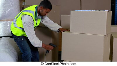 Warehouse worker scanning barcodes on boxes in a large...