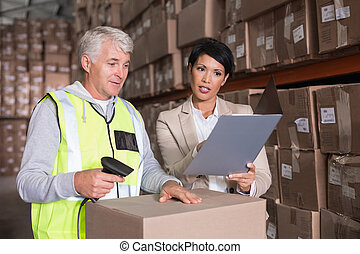 Warehouse worker scanning box with manager in a large...