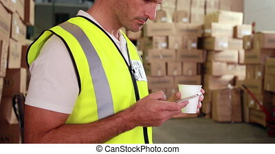 Warehouse worker sending a text on his break in a warehouse