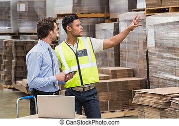 Warehouse worker showing something to his manager