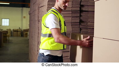 Warehouse worker stacking cardboard boxes in a warehouse