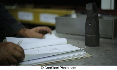 warehouse worker standing at the desk and take notes in the Journal of the cargo arrived at the warehouse