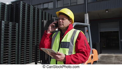 Warehouse worker talking on phone outside factory - Side ...