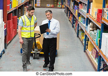 Warehouse worker talking with his manager in a large...