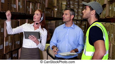 Warehouse worker talking with management in a large...