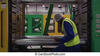 Warehouse worker using a digital tablet - Side view of ...