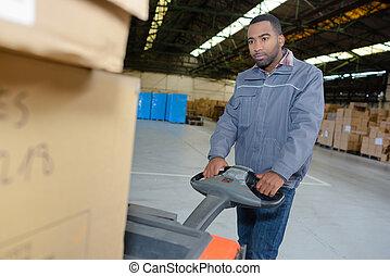 Warehouse worker using pallet truck