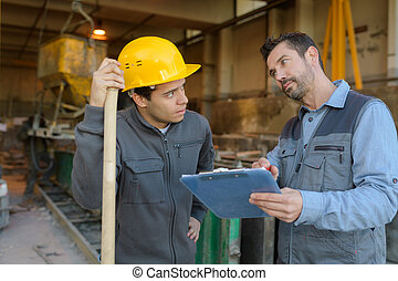 warehouse workers discussing clipboard planning