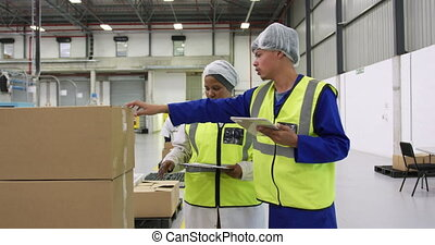 Warehouse workers discussing together - Side view of focused...