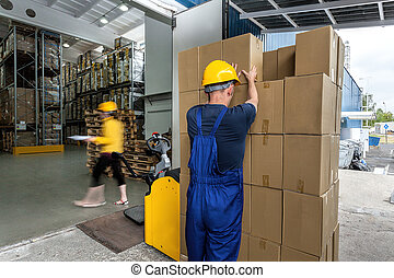 Warehouse workers doing their work - export of packages with...