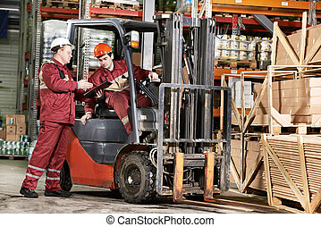 warehouse workers in front of forklift - young warehouse...