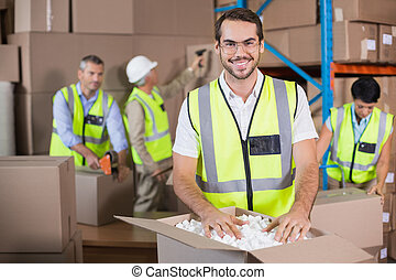 Warehouse workers in yellow vests preparing a shipment in a ...