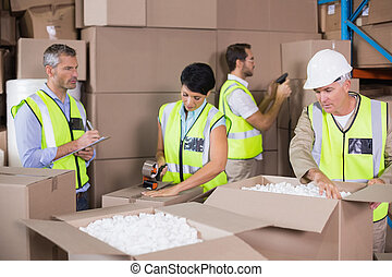 Warehouse workers in yellow vests preparing a shipment in a large warehouse