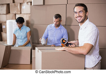 Warehouse workers preparing a shipment in a large warehouse