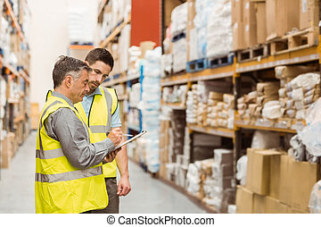Warehouse workers talking together at work in a large warehouse