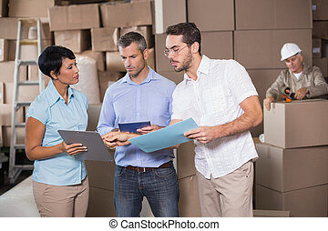 Warehouse workers talking together at work