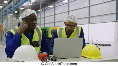 Warehouse workers using laptop in factory - Front view close...