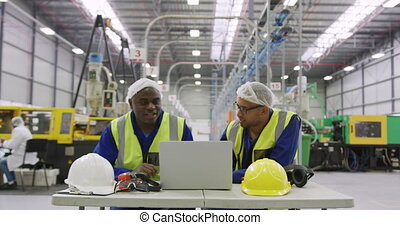 Warehouse workers using laptop in factory - Front view of a ...