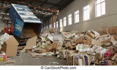 Warehouses with recyclable materials at the garbage processing factory. Truck brought the waste paper to the garbage processing plant. Large warehouse of waste paper in a factory.