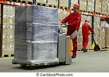 Warehousing - people at work - Two workers in uniforms and...