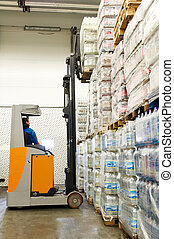 warehousing truck at work - Worker driver of a forklift ...