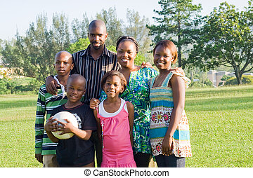 warm african family - african mom and dad and kids in park