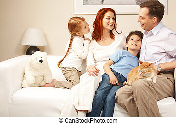 Friendly family members sitting on comfortable sofa and communicating at home