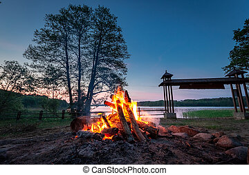 Warm bonfire at dusk by the lake in summer