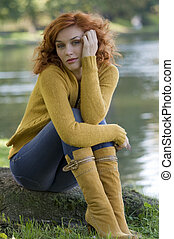 pretty and young woman posing near a river in fall season