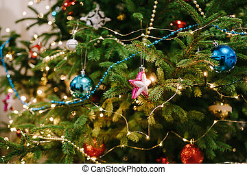 Warm cozy background of a decorated Christmas tree with balls on the branches.