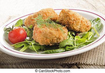 warm fish cake with tomato on green salad