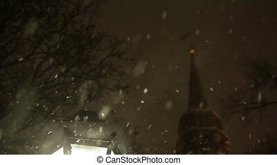 Warm Glow of Street Light Surrounded by Snowflakes in First Snowfall of the Winter Season