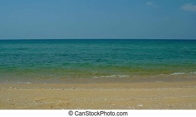 Warm Ocean Water laps at Coarse Sand on a Tropical Beach -...
