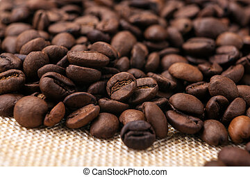 warm roasted coffee beans on burlap close up - roasted ...