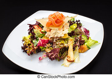 warm salad of fish, vegetables on a white plate