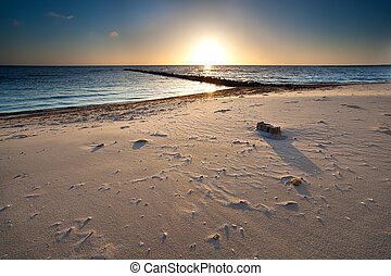 warm sunset over sand beach on North sea
