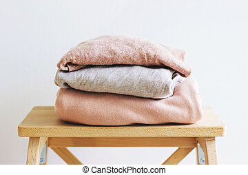 Warm sweaters lie on a wooden shelf.