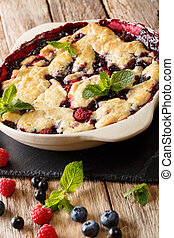 warm sweet cobbler of raspberries and blueberries close-up in a baking dish. vertical