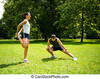 Warm up - couple exercising before jogging - Young couple...