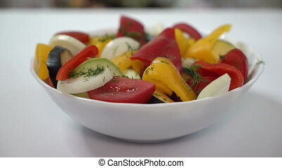 Warm vegetable salad. Bowl with mixed fresh vegetables on dining table.