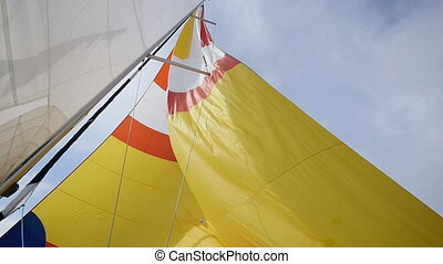 Warm wind blows in colorful sail on background of sky on the island of Crete.
