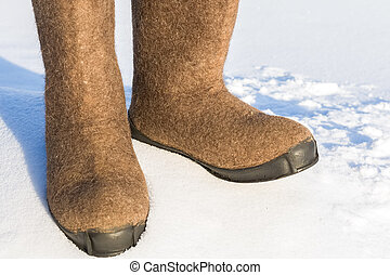 Warm winter shoes made of felt close up in the snow. Photo outdoors on a frosty day