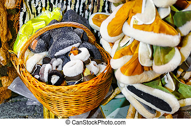 Warm woolen slippers displayed for sale at stall during Christmas market in Riga, Latvia. Wool socks with shoes in winter. Street Xmas and holiday fair. Advent Decoration with Crafts Items on Bazaar