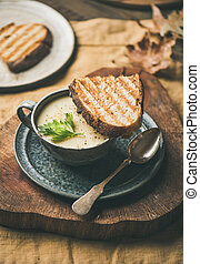 Warming celery cream soup and toast over linen tablecloth