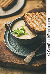 Warming celery cream soup and toast over linen tablecloth, close-up