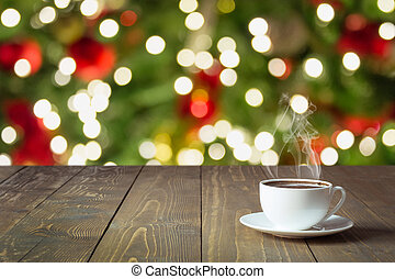 Warming cup of black coffee on wooden table. Blurred christmas tree as background. Christmas Time.