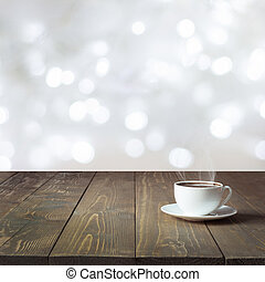 Warming cup of hot black coffee on wooden table in cafe. Blurred light white as background. Image for display or montage your products.