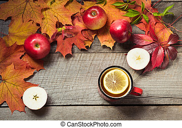 Warming cup of tea, decor of autumn leaves, apples on wooden board. Fall still life. Top view.