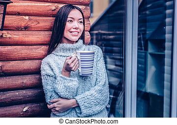 Positive young woman holding a mug with coffee