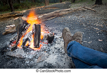 Warming Feet by Campfire - Person warms their feet next to a...